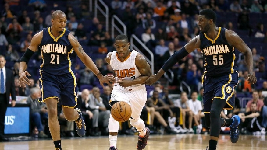 Phoenix Suns guard Eric Bledsoe, center, pushes the ball up court against Indiana Pacers forward David West (21) and Roy Hibbert (55) during the second half of an NBA basketball game, Tuesday, Dec. 2, 2014, in Phoenix. The Suns won 116-99. (AP Photo/Matt York)