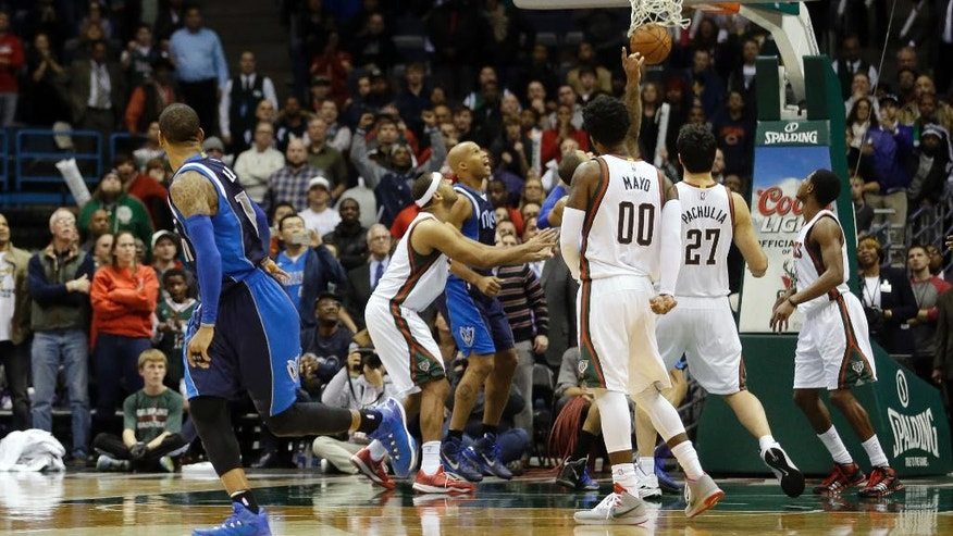 Dallas Mavericks' Monta Ellis, left, watches his game-winning shot go in as time runs out during the second half of an NBA basketball game against the Milwaukee Bucks Wednesday, Dec. 3, 2014, in Milwaukee. The Mavericks won 107-105. (AP Photo/Morry Gash)