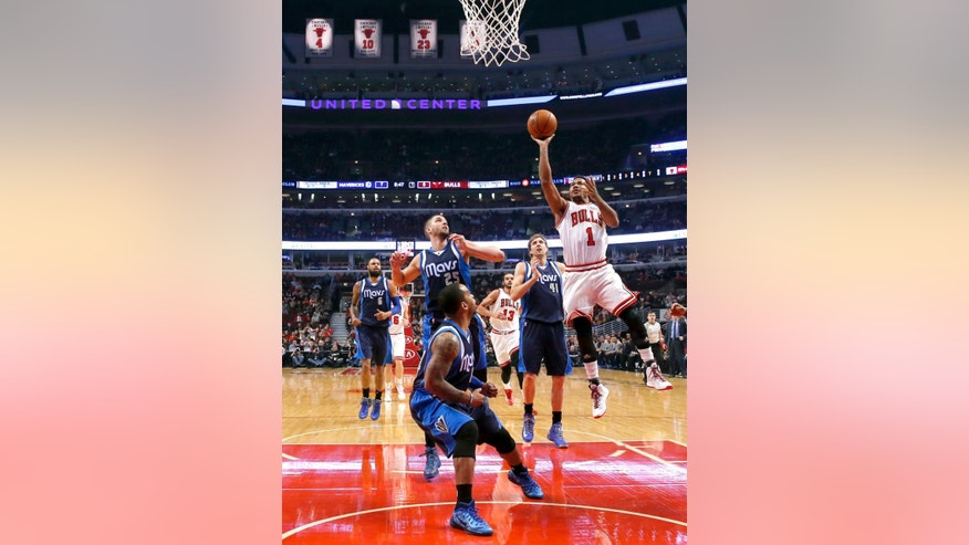 Chicago Bulls guard Derrick Rose (1) shoots over Dallas Mavericks' Chandler Parsons (25) Jameer Nelson, center, and Dirk Nowitzki (41) during the first half of an NBA basketball game Tuesday, Dec. 2, 2014, in Chicago. (AP Photo/Charles Rex Arbogast)