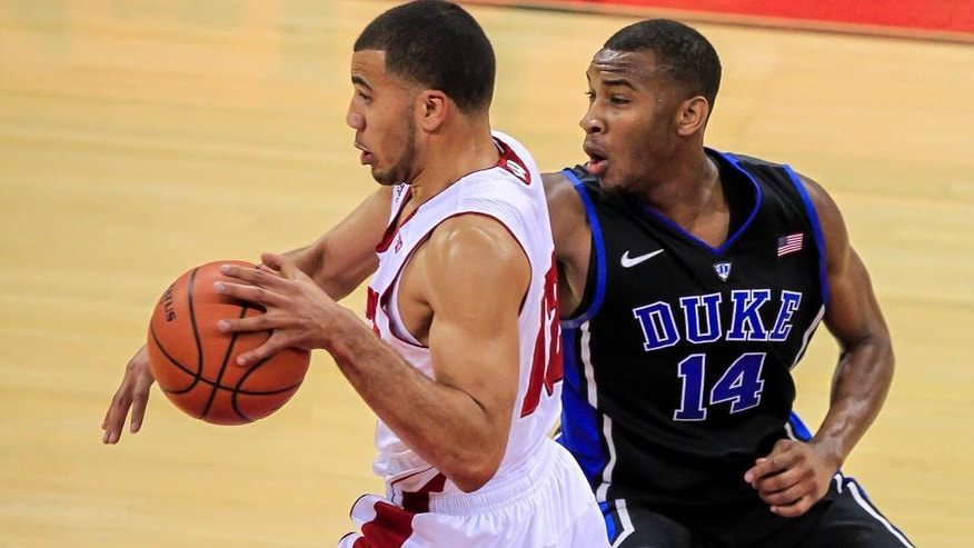 Duke's Rasheed Sulaimon (14) reaches in on Wisconsin's Traevon Jackson during the first half of an NCAA college basketball game Wednesday, Dec. 3, 2014, in Madison, Wis. (AP Photo/Andy Manis)