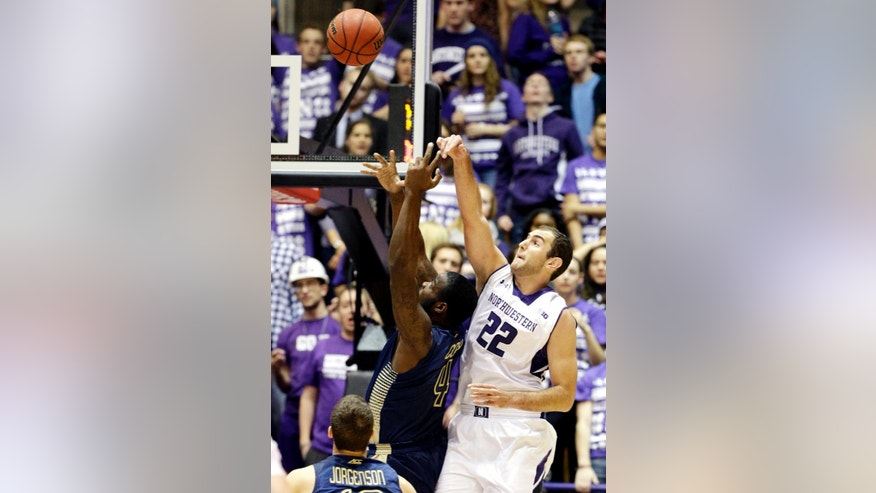 Northwestern center Alex Olah (22) and Georgia Tech center Demarco Cox (4) battle for a rebound during the first half of an NCAA college basketball game in Evanston, Ill., on Wednesday, Dec. 3, 2014. (AP Photo/Nam Y. Huh)