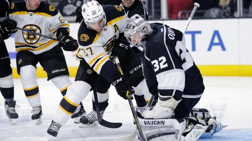Los Angeles Kings goalie Jonathan Quick, right, stops a shot by Boston Bruins' Patrice Bergeron, center, as Kings' Anze Kopitar, top center, of Slovenia, watches during the first period of an NHL hockey game Tuesday, Dec. 2, 2014, in Los Angeles. (AP Photo/Jae C. Hong)