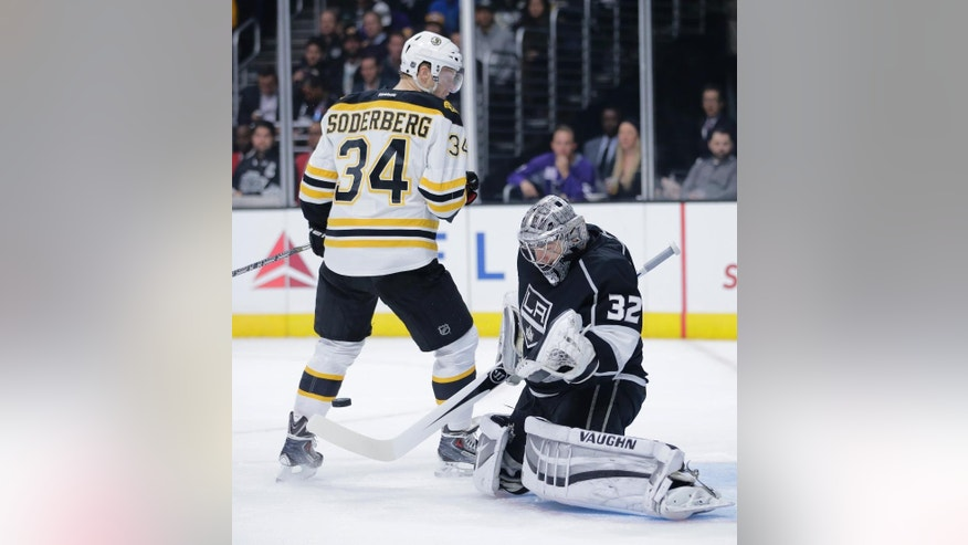 Los Angeles Kings goalie Jonathan Quick, right, deflects a puck as Boston Bruins' Carl Soderberg watches during the first period of an NHL hockey game Tuesday, Dec. 2, 2014, in Los Angeles. (AP Photo/Jae C. Hong)