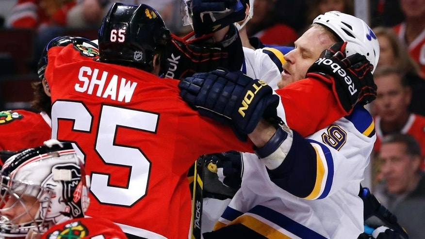 Chicago Blackhawks center Andrew Shaw (65) and St. Louis Blues center Steve Ott get into a shoving match during the first period of an NHL hockey game Wednesday, Dec. 3, 2014, in Chicago. (AP Photo/Charles Rex Arbogast)