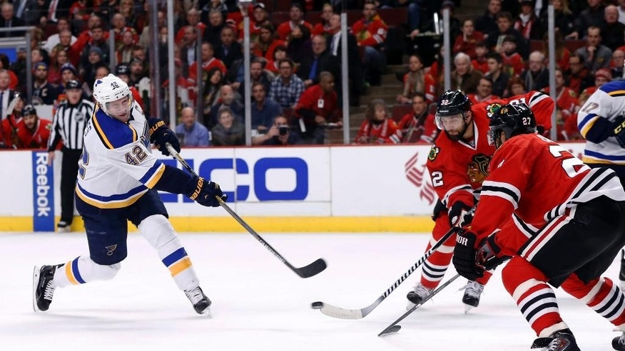 St. Louis Blues center David Backes (42) takes a shot on goal past Chicago Blackhawks defenseman Duncan Keith (2) and Johnny Oduya (27) during the first period of an NHL hockey game Wednesday, Dec. 3, 2014, in Chicago. (AP Photo/Charles Rex Arbogast)
