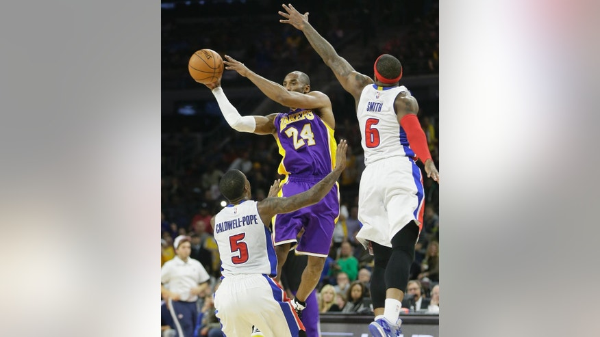 Los Angeles Lakers guard Kobe Bryant (24) passes the ball defended by Detroit Pistons guard Kentavious Caldwell-Pope (5) and forward Josh Smith (6) during the second half of an NBA basketball game in Auburn Hills, Mich., Tuesday, Dec. 2, 2014. Bryant scored 12 straight points in the third quarter and the Lakers defeated the Pistons 106-96. (AP Photo/Carlos Osorio)