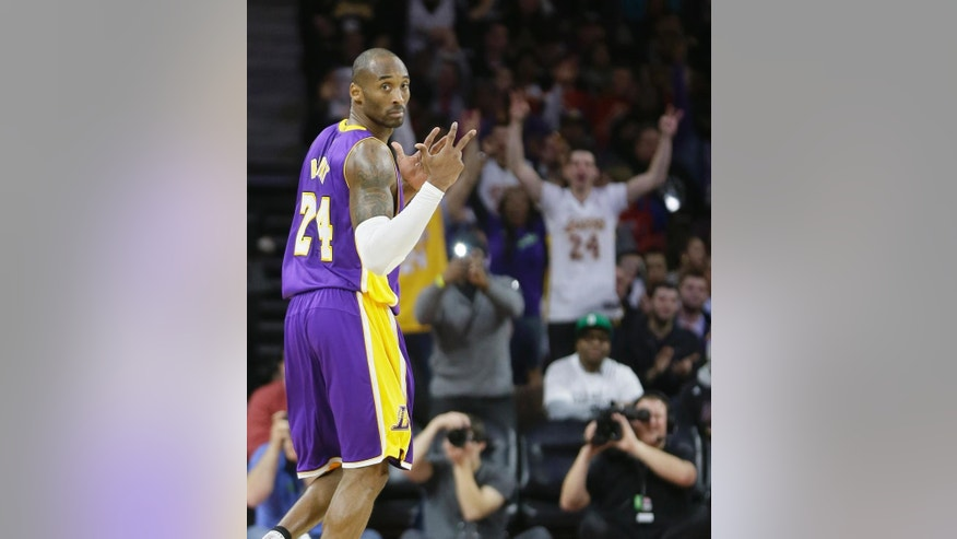 Los Angeles Lakers guard Kobe Bryant signals and a Lakers fan cheers after Bryant's three point basket during the second half of an NBA basketball game against the Detroit Pistons in Auburn Hills, Mich., Tuesday, Dec. 2, 2014. The Lakers defeated the Pistons 106-96. (AP Photo/Carlos Osorio)