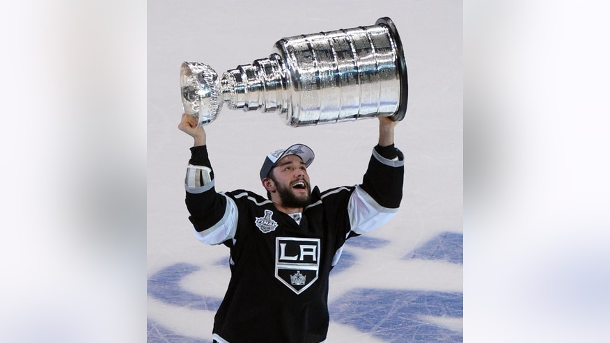 FILE - In this June 13, 2014, file photo, Los Angeles Kings defenseman Alec Martinez carries the Stanley Cup after the Kings defeated the New York Rangers in Game 5 of the NHL hockey Stanley Cup finals in Los Angeles. The Kings agreed to a six-year, $24 million contract extension with Martinez Wednesday, Dec. 3, 2014. (AP Photo/Mark J. Terrill, File)