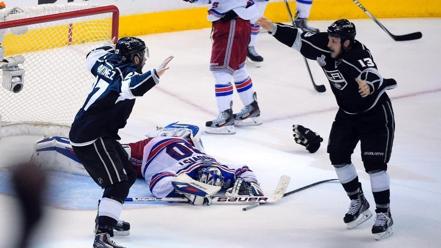FILE - In this June 13, 2014, file photo, the gloves come off as Los Angeles Kings defenseman Alec Martinez, left, and teammate left wing Kyle Clifford celebrate as New York Rangers goalie Henrik Lundqvist, of Sweden, lies on the ice after the Kings defeated the Rangers in overtime in Game 5 of the NHL Stanley Cup Final series in Los Angeles. The Kings agreed to a six-year, $24 million contract extension with Martinez, Wednesday, Dec. 3, 2014. (AP Photo/Mark J. Terrill, File)