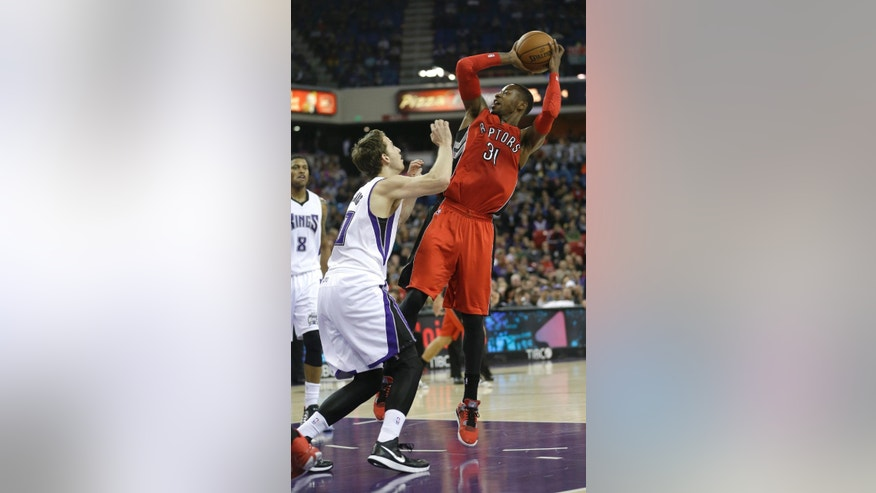 Toronto Raptors guard Terrence Ross, right, shoots over Sacramento Kings guard Nik Stauskas, of Canada, during the first quarter of an NBA basketball game in Sacramento, Calif., Tuesday, Dec. 2, 2014.(AP Photo/Rich Pedroncelli)