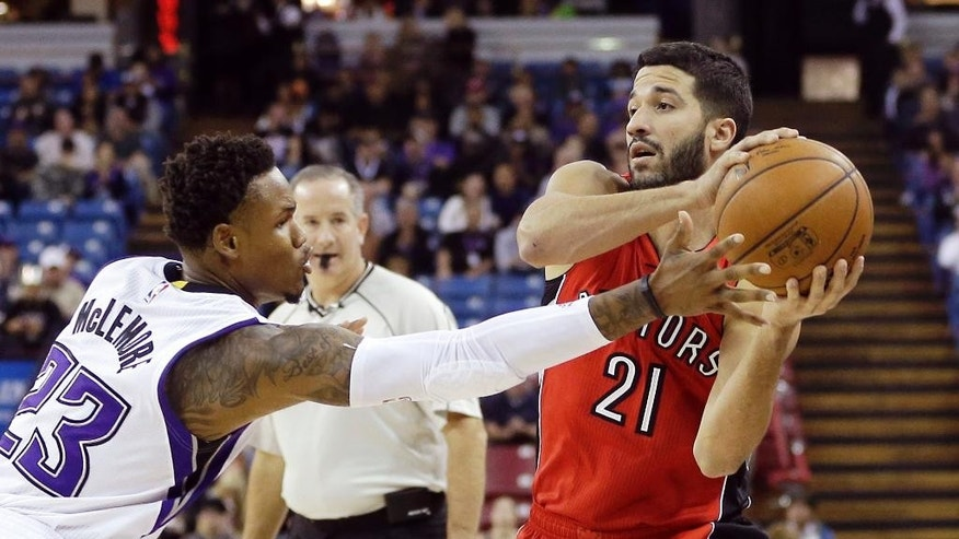 Toronto Raptors guard Greivis Vasquez, right, of Venezuela, protects the ball from   Sacramento Kings guard Ben McLemore during the first quarter of an NBA basketball game in Sacramento, Calif., Tuesday, Dec. 2, 2014.(AP Photo/Rich Pedroncelli)