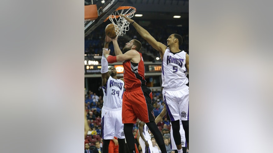 Toronto Raptors center Jonas Valanciunas, of Lithuania, center, goes to the basket between Sacramento Kings' Jason Thompson, left, and Ryan Hollins during the first quarter of an NBA basketball game in Sacramento, Calif., Tuesday, Dec. 2, 2014.(AP Photo/Rich Pedroncelli)