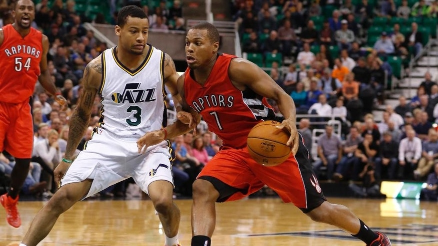 Toronto Raptors guard Kyle Lowry (7) drives for a shot attempt while defended by Utah Jazz guard Trey Burke (3) during the first half of an NBA basketball game, Wednesday, Dec. 3, 2014 in Salt Lake City. (AP Photo/Jim Urquhart)