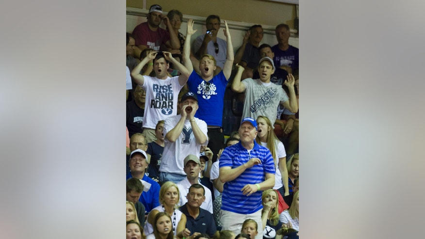 In this Nov. 26, 2014, photo, BYU fans disagree with a game official's call in the second half of an NCAA college basketball game against Purdue at the Maui Invitational in Lahaina, Hawaii. Brigham Young's basketball team has a built-in home crowd advantage nearly every place it goes. Sometimes it's a small, vocal group in the corner, other times several hundred fans show up, outnumbering those there to support the actual home team. (AP Photo/Eugene Tanner)