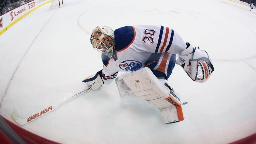 Edmonton Oilers goaltender Ben Scrivens (30) scrambles to get his stick in the corner against the Winnipeg Jets during second period NHL action in Winnipeg, Manitoba, on Wednesday, Dec. 3, 2014. (AP Photo/The Canadian Press, John Woods)