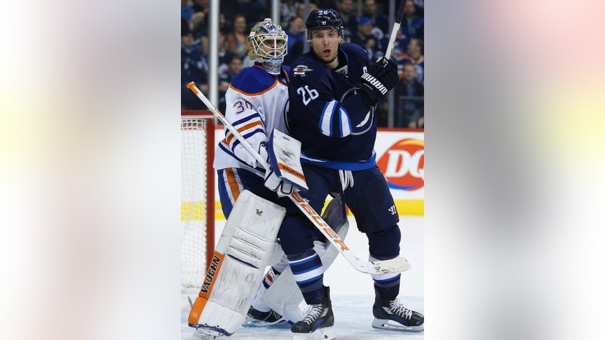 Winnipeg Jets' Blake Wheeler (26) fights for position in front of Edmonton Oilers goaltender Ben Scrivens (30) during second period NHL action in Winnipeg, Manitoba, on Wednesday, Dec. 3, 2014. (AP Photo/The Canadian Press, John Woods)