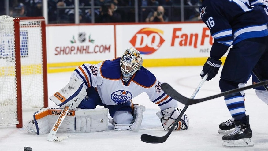 Edmonton Oilers goaltender Ben Scrivens (30) saves the shot from Winnipeg Jets' Andrew Ladd (16) during second period NHL action in Winnipeg, Manitoba, on Wednesday, Dec. 3, 2014. (AP Photo/The Canadian Press, John Woods)