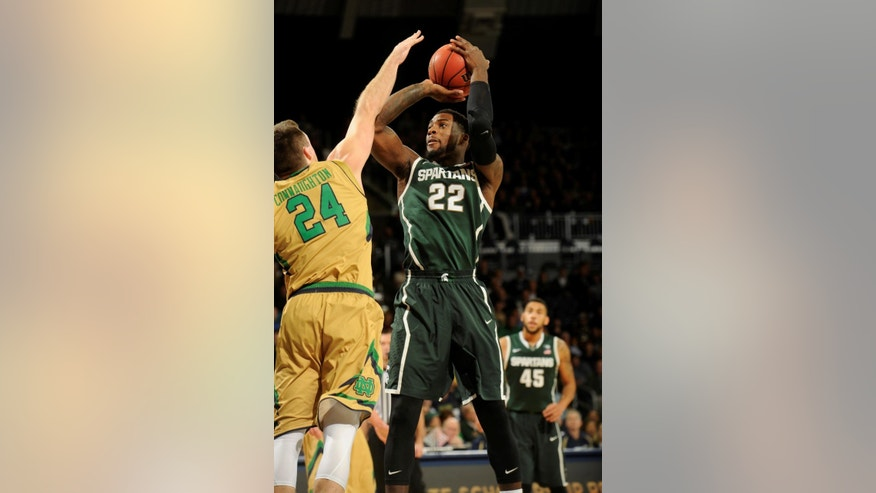 Michigan State forward Branden Dawson, right, shoots over Notre Dame guard Pat Connaughton during first-half action in an NCAA college basketball game Wednesday Dec. 3, 2014, in South Bend, Ind. (AP Photo/Joe Raymond)
