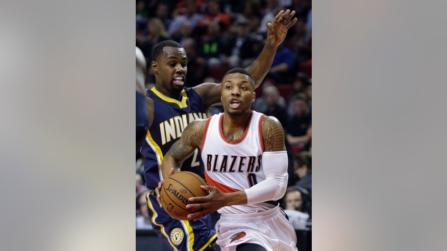 Portland Trail Blazers guard Damian Lillard, right, drives past Indiana Pacers guard Rodney Stuckey during the first half of an NBA basketball game in Portland, Ore., Thursday, Dec. 4, 2014.(AP Photo/Don Ryan)