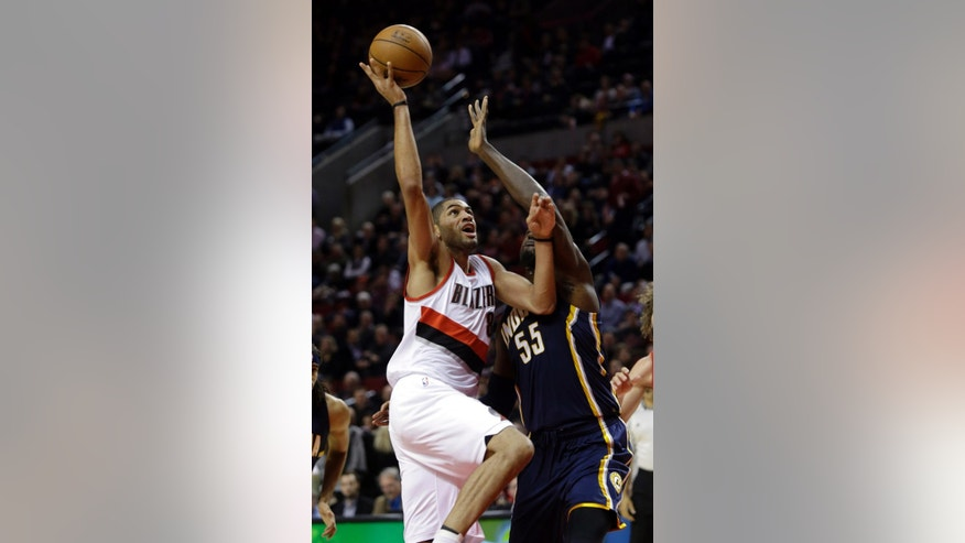 Portland Trail Blazers forward Nicolas Batum, from France,, left, drives to the basket against Indiana Pacers center Roy Hibbert during the first half of an NBA basketball game in Portland, Ore., Thursday, Dec. 4, 2014.(AP Photo/Don Ryan)