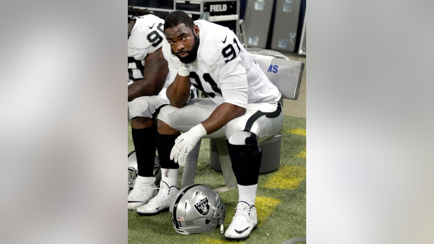 Oakland Raiders defensive end Justin Tuck sits on the bench during the fourth quarter of an NFL football game against the St. Louis Rams, Sunday, Nov. 30, 2014, in St. Louis. (AP Photo/Tom Gannam)
