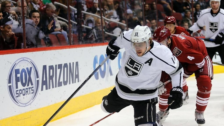 Los Angeles Kings center Anze Kopitar (11) is checked from behind by Arizona Coyotes defenseman Zbynek Michalek (4) in the first period during an NHL hockey game, Thursday, Dec. 4, 2014, in Glendale, Ariz. (AP Photo/Rick Scuteri)