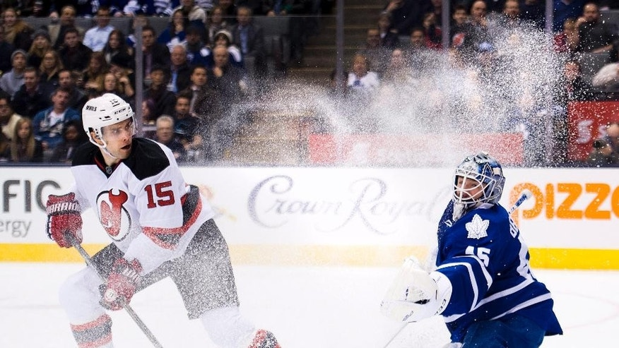 Toronto Maple Leafs goalie Jonathan Bernier, right, gets snowed from New Jersey Devils forward Tuomo Ruutu (15) during the first period of an NHL hockey game, Thursday, Dec. 4, 2014 in Toronto. (AP Photo/The Canadian Press, Nathan Denette)