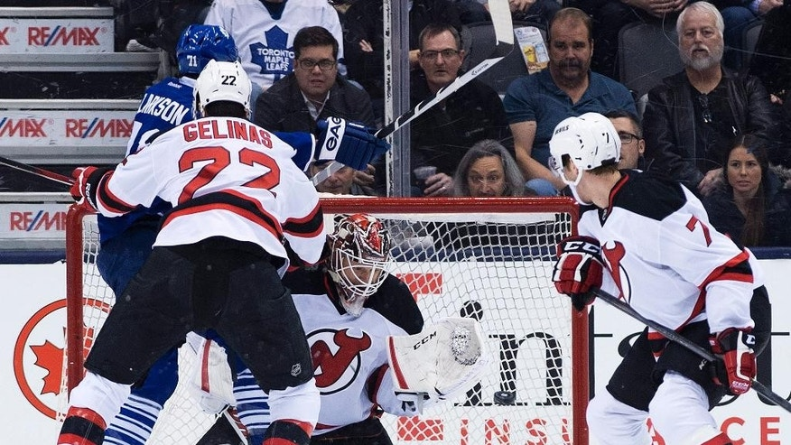 New Jersey Devils goalie Cory Schneider, center, makes a save as his teammates Jon Merrill (7) and Eric Gelinas (22) clear out Maple leafs forward David Clarkson (71) during the first period of an NHL hockey game, Thursday, Dec. 4, 2014 in Toronto. (AP Photo/The Canadian Press, Nathan Denette)