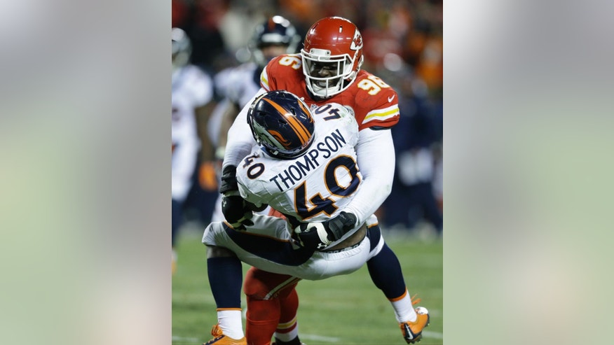 Denver Broncos running back Juwan Thompson (40) is tackled by Kansas City Chiefs defensive end Jaye Howard (96) in the second half of an NFL football game in Kansas City, Mo., Sunday, Nov. 30, 2014. (AP Photo/Ed Zurga)