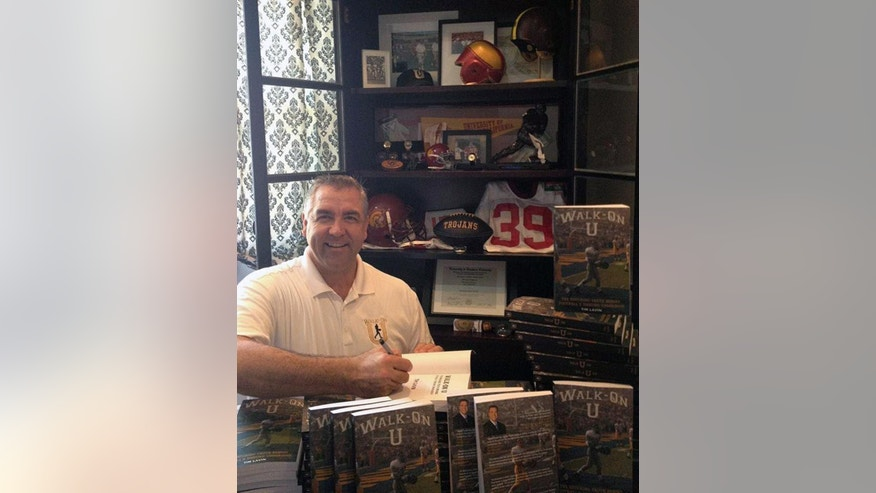 "In this Oct. 2013, photo provided by Tim Lavin, Tim Lavin, a former walk-on at Southern California, signs copies of his book at his home in Hunting Beach, Calif. Coaches and players say walk-ons like Ohio State's Kosta Karageorge _ who was found dead of an apparently self-inflicted gunshot on Sunday, Nov. 30, 2014,  are treated just as well as their highly recruited teammates. Lavin wrote a book last year titled ""Walk-On U: The Shocking Truth Behind Football's Unsung Underdogs."" He also has a Web site (www.walk-onu.com) with news stories on walk-ons and recently circulated a petition calling for better treatment of walk-ons.  (AP Photo/Courtesy of Tim Lavin)"