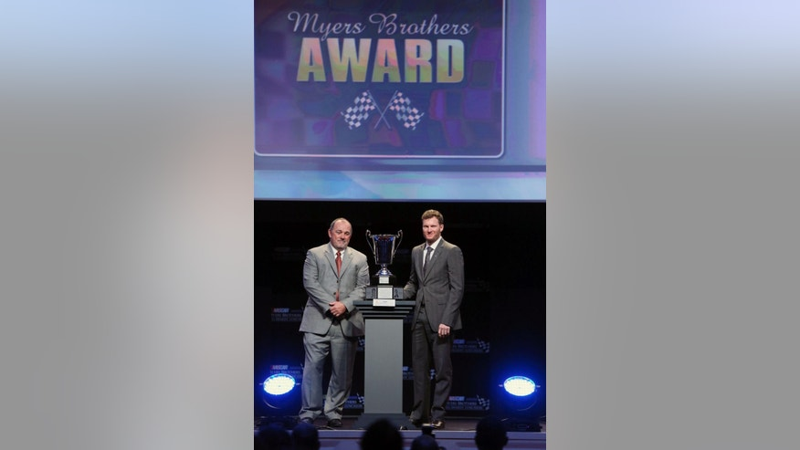 Kenny Bruce, left, president of National Motorsports Press Association, and Dale Earnhardt Jr. stand with Earnhardt's NMPA Myers Brothers award during the NASCAR NMPA Myers Brothers Awards Luncheon, Thursday, Dec. 4, 2014, in Las Vegas. NASCAR drivers are in Las Vegas for Champion's Week. (AP Photo/Ronda Churchill)