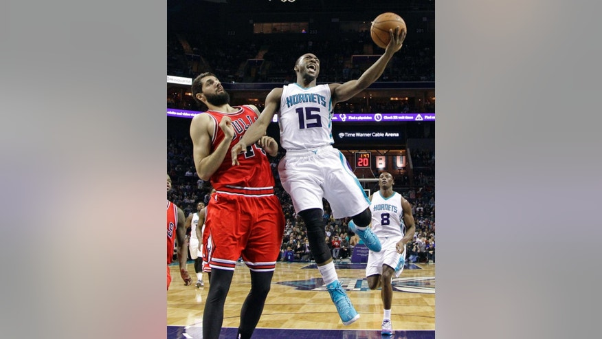 Charlotte Hornets' Kemba Walker, right, drives past Chicago Bulls' Nikola Mirotic, left, during the second half of an NBA basketball game in Charlotte, N.C., Wednesday, Dec. 3, 2014. The Bulls won 102-95. (AP Photo/Chuck Burton)