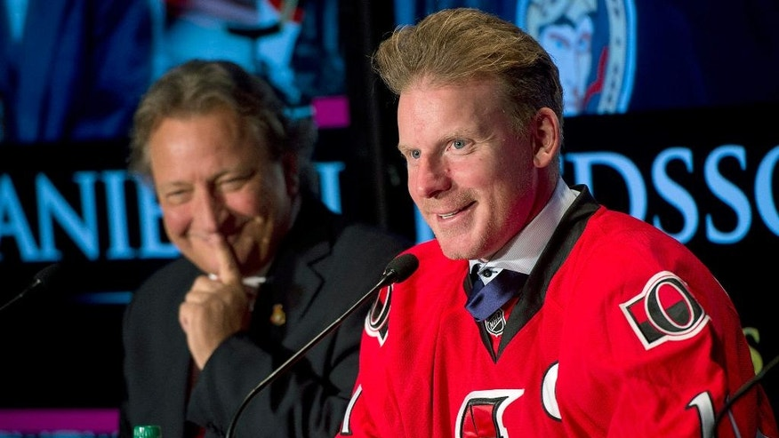 Ottawa Senators owner Eugene Melnyk looks on as former Senators captain Daniel Alfredsson speaks during an NHL hockey news conference announcing his retirement, Thursday, Dec. 4, 2014 in Ottawa.  The Senators signed their longtime captain to a one-day contract so he can skate in pre-game warm-ups with the team one last time tonight and take a ceremonial faceoff before they play the New York Islanders. (AP Photo/The Canadian Press, Adrian Wyld)