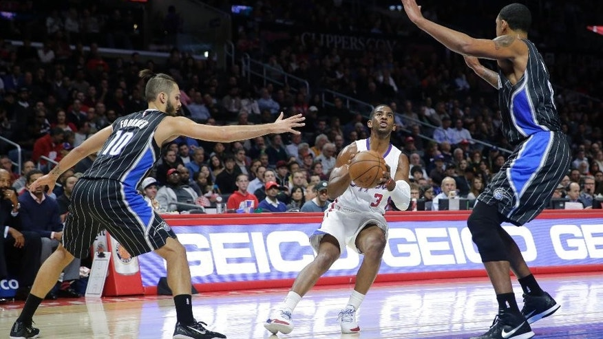 Los Angeles Clippers' Chris Paul, center, looks to shoot between Orlando Magic's Evan Fournier, left, and Kyle O'Quinn during the first half of an NBA basketball game Wednesday, Dec. 3, 2014, in Los Angeles. (AP Photo/Jae C. Hong)