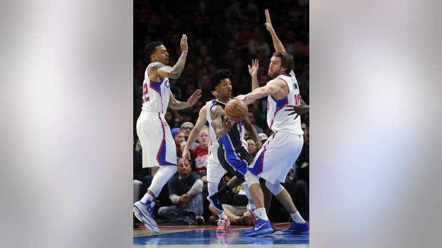 Orlando Magic's Elfrid Payton, center, passes the ball as he is defended by Los Angeles Clippers' Spencer Hawes, right, and Matt Barnes during the first half of an NBA basketball game Wednesday, Dec. 3, 2014, in Los Angeles. (AP Photo/Jae C. Hong)