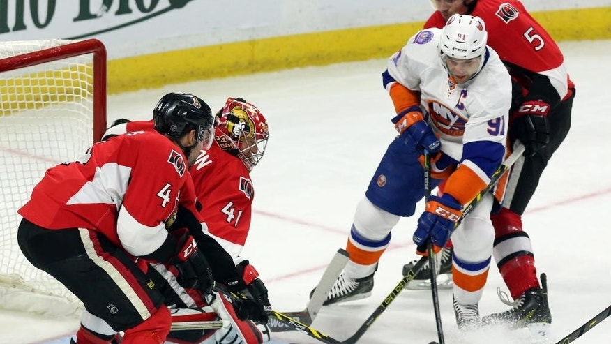 New York Islanders' John Tavares (91) battles for the puck with Ottawa Senators' Cody Ceci (5) and Chris Phillips (4) as Senators goaltender Craig Anderson (41) looks on during second-period NHL hockey game action in Ottawa, Ontario, Thursday, Dec. 4, 2014. (AP Photo/The Canadian Press, Fred Chartrand)