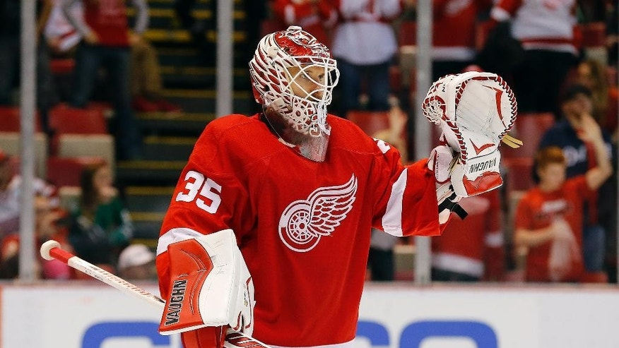 Detroit Red Wings goalie Jimmy Howard (35) celebrates after his team defeated the Dallas Stars 5-2 after an NHL hockey game in Detroit, Thursday, Dec. 4, 2014. (AP Photo/Paul Sancya)