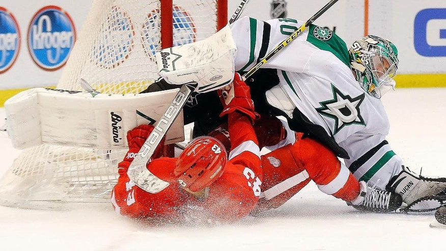 Detroit Red Wings center Darren Helm (43) collides with Dallas Stars goalie Jussi Rynnas (40) in the second period during an NHL hockey game in Detroit Thursday, Dec. 4, 2014. (AP Photo/Paul Sancya)