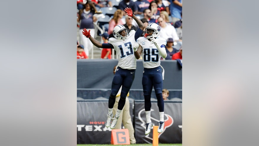 Tennessee Titans' Kendall Wright (13) celebrates his touchdown catch with teammate Nate Washington (85) during the second half of an NFL football game against the Houston Texans Sunday, Nov. 30, 2014, in Houston. (AP Photo/Eric Gay)