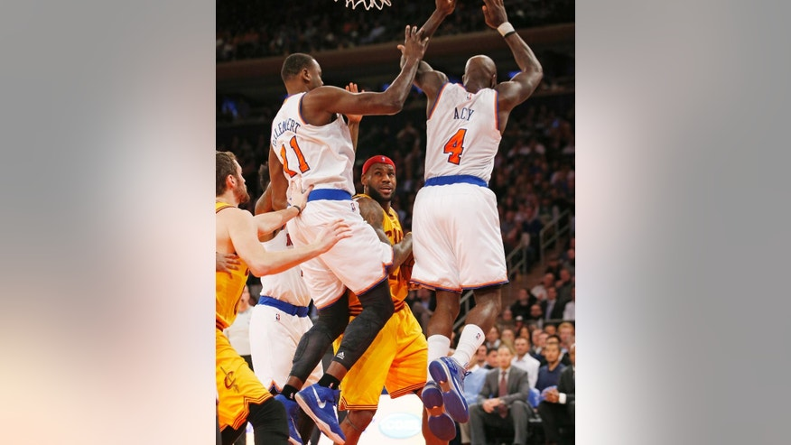 New York Knicks center Samuel Dalembert (11) and New York Knicks forward Quincy Acy (4) double team Cleveland Cavaliers forward LeBron James (23) in the first half of an NBA basketball game at Madison Square Garden in New York, Thursday, Dec. 4, 2014. (AP Photo/Kathy Willens)