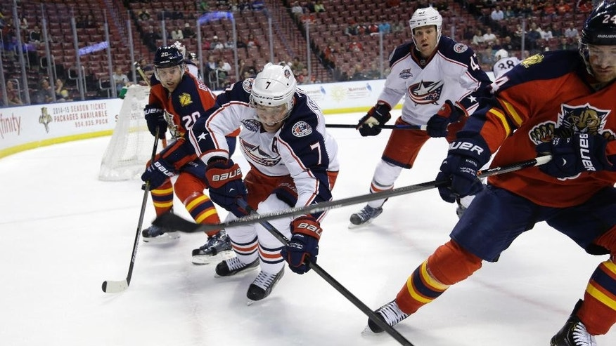 Columbus Blue Jackets defenseman Jack Johnson (7) goes for the puck as Florida Panthers left wing Sean Bergenheim looks on during the second period of an NHL hockey game, Thursday, Dec. 4, 2014, in Sunrise, Fla. (AP Photo/Lynne Sladky)