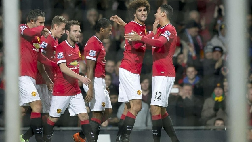 Manchester United's Marouane Fellaini, second right, celebrates scoring with teammates during the English Premier League soccer match between Manchester United and Stoke City at Old Trafford Stadium, Manchester, England, Tuesday Dec. 2, 2014. (AP Photo/Jon Super)