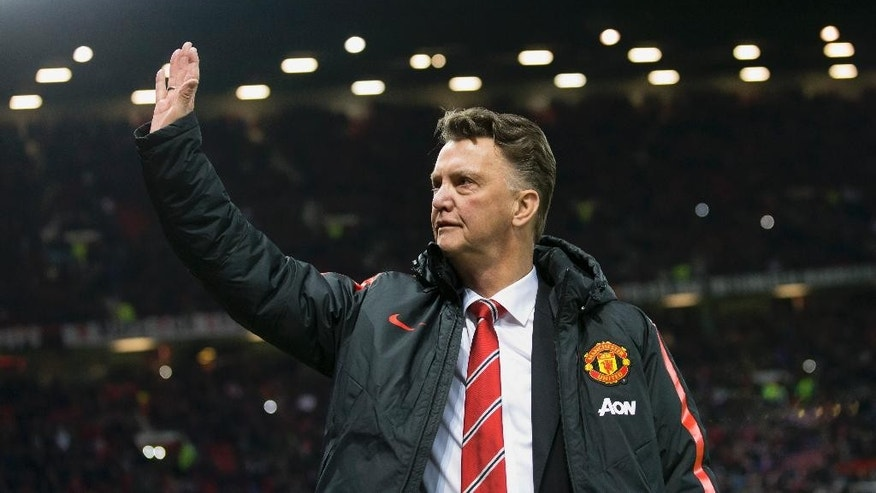 Manchester United manager Louis van Gaal waves to supporters before the English Premier League soccer match between Manchester United and Stoke City at Old Trafford Stadium, Manchester, England, Tuesday Dec. 2, 2014. (AP Photo/Jon Super)