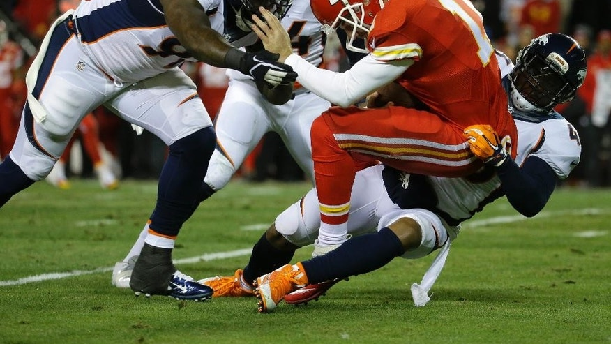 Kansas City Chiefs quarterback Alex Smith (11) is tackled by Denver Broncos strong safety T.J. Ward, right, Denver Broncos defensive end DeMarcus Ware, top, and Denver Broncos defensive end Malik Jackson, left, in the first half of an NFL football game in Kansas City, Mo., Sunday, Nov. 30, 2014. (AP Photo/Charlie Riedel)