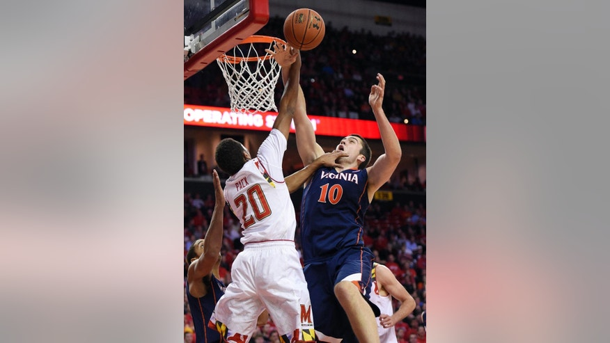 Maryland guard Richaud Pack (20) goes to the basket against Virginia forward/center Mike Tobey (10) during the second half of an NCAA college basketball game, Wednesday, Dec. 3, 2014, in College Park, Md. Virginia won 76-65. (AP Photo/Nick Wass)