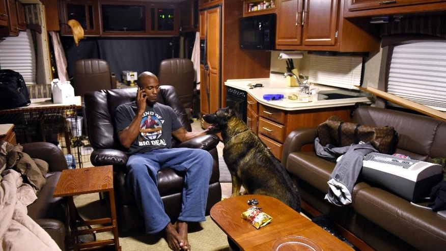 FILE - In this Oct. 15, 2014, file photo, former Minnesota Timberwolves forward Dante Cunningham talks on his cell phone as he spends time with his dog, Ruger, in Cunningham's motor home in Bellefonte, Pa. Cunningham is living in the motor home as he continues to train. The New Orleans Pelicans have signed Cunningham, who has struggled to clear his name after domestic assault charges against him were dropped this summer.  (AP Photo/John Beale, File)