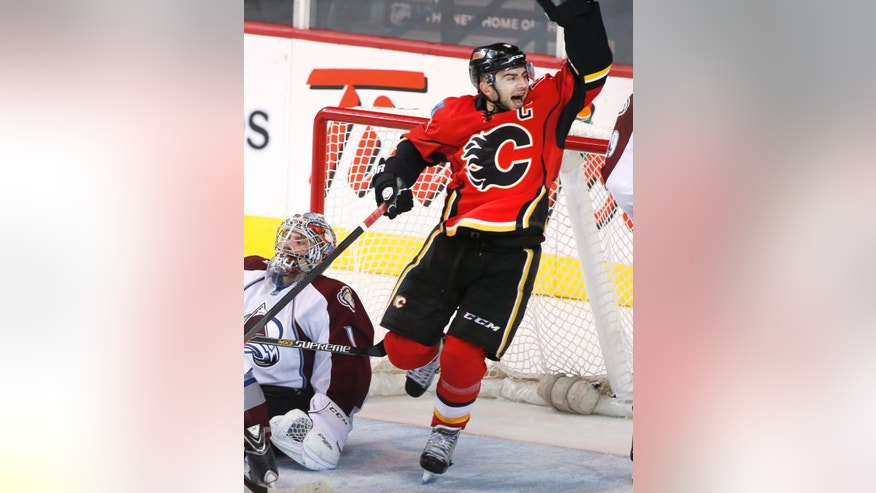 Calgary Flames' Mark Giordano, right, celebrates Sean Monahan's winning overtime goal against Colorado Avalanche goalie Semyon Varlamov, from Russia, during overtime in an NHL hockey game, Thursday, Dec. 4, 2014 in Calgary, Alberta. (AP Photo/The Canadian Press, Larry MacDougal)