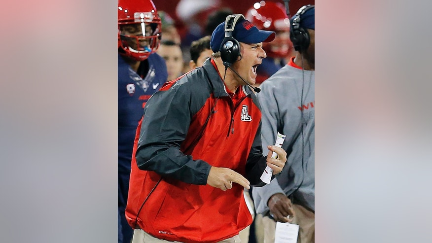 FILE - In this Nov. 8, 2014, file photo, Arizona coach Rich Rodriguez reacts to a play against Colorado during the second half of an NCAA college football game in Tucson, Ariz.  Arizona was a program in disarray when Rich Rodriguez took over as coach. Three years later, the eighth-ranked Wildcats won the Pac-12 South and playing for a conference championship, a rapid rise not even Rodriguez saw coming. (AP Photo/Rick Scuteri, File)