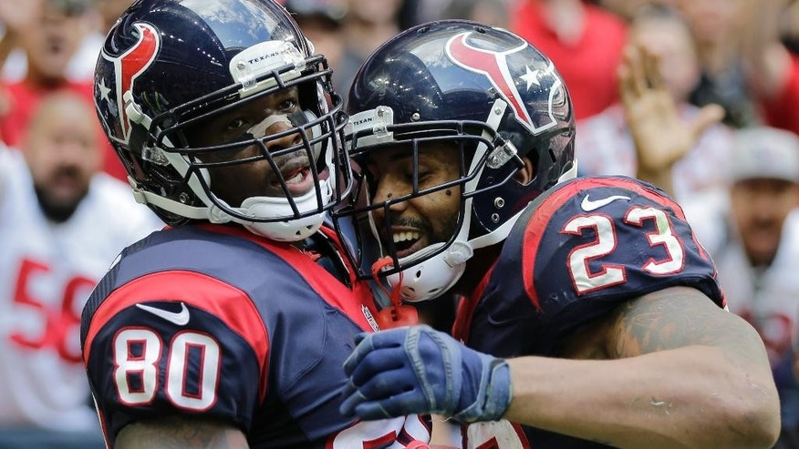 Houston Texans' Andre Johnson (80) celebrates with teammate Arian Foster (23) after he caught a pass for a touchdown against the Tennessee Titans during the second half of an NFL football game Sunday, Nov. 30, 2014, in Houston. Houston won 45-21. (AP Photo/Eric Gay)