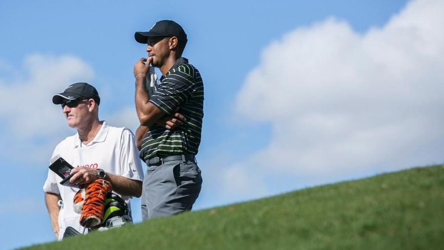 Tiger Woods and his caddie Joe LaCava look toward the green on the seventh hole during the first round of the Hero World Challenge golf tournament on Thursday, Dec. 4, 2014, in Windermere, Fla. (AP Photo/Willie J. Allen Jr.)